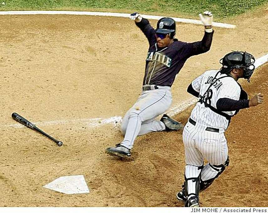 Seattle Mariners' Rickey Henderson comes home past Chicago White Sox catcher Charles Johnson on a Alex Rodriguez sacrifice during the fifth inning of game two of the American League division series in Chicago, Wednesday, Oct. 4, 2000. Photo: JIM MONE, Associated Press