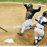 Seattle Mariners' Rickey Henderson comes home past Chicago White Sox catcher Charles Johnson on a Alex Rodriguez sacrifice during the fifth inning of game two of the American League division series in Chicago, Wednesday, Oct. 4, 2000.