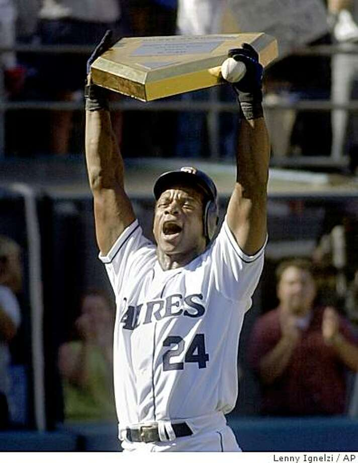 In this Oct. 4, 2001 file photo, San Diego Padres' Rickey Henderson holds up a gold-plated commemorative home plate presented to him after he scored his 2,246 career run by hitting a home run in the third inning against the Los Angeles Dodgers in San Diego. The run broke baseball's all-time record set by Ty Cobb in 1928. Henderson and Jim Rice were elected to the baseball Hall of Fame Monday Jan. 12, 2009. Photo: Lenny Ignelzi, AP