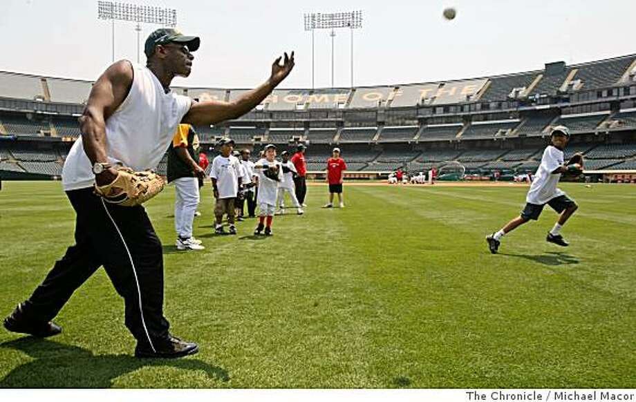 2008: Former Oakland Athletic star Rickey Henderson tosses balls to kids of the Oakland Babe Ruth Baseball League, during the Bak of America Youth Baseball Clinic at the McAfee Coliseum in Oakland, Calif. of Tuesday July 8, 2008.  Photo: Michael Macor, The Chronicle