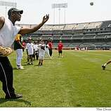 Former Oakland Athletic star Rickey Henderson tosses balls to kids of the Oakland Babe Ruth Baseball League, during the Bak of America Youth Baseball Clinic at the McAfee Coliseum in Oakland, Calif. of TUesday July 8, 2008. Photo By Michael Macor/ The Chronicle