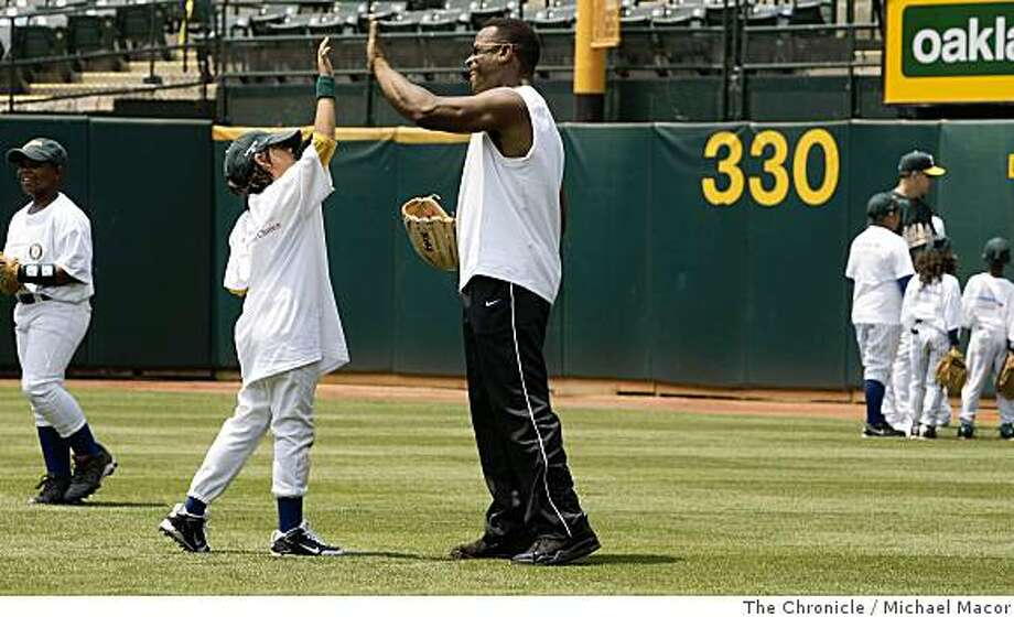 Former Oakland Athletic star Rickey Henderson gets a high-five from Albert Ybarra, 9 of Oakland ,during the Bank of America Youth Baseball Clinic at the McAfee Coliseum in Oakland, Calif.,  on Tuesday July 8, 2008.Photo By Michael Macor/ The Chronicle Photo: Michael Macor, The Chronicle