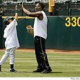 Former Oakland Athletic star Rickey Henderson gets a high-five from Albert Ybarra, 9 of Oakland ,during the Bank of America Youth Baseball Clinic at the McAfee Coliseum in Oakland, Calif.,  on Tuesday July 8, 2008.Photo By Michael Macor/ The Chronicle
