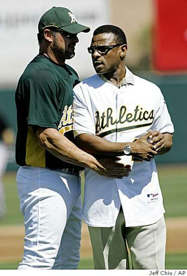 Hall of Famer and former Oakland Athletics' Rickey Henderson, right, talks with Athletics' Jason Giambi after throwing the ceremonial first pitch, caught by Giambi, before the Athletics played the San Francisco Giants in a spring training baseball game in Phoenix, Saturday, March 14, 2009. (AP Photo/Jeff Chiu) Photo: Jeff Chiu, AP