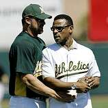 Hall of Famer and former Oakland Athletics' Rickey Henderson, right, talks with Athletics' Jason Giambi after throwing the ceremonial first pitch, caught by Giambi, before the Athletics played the San Francisco Giants in a spring training baseball game in Phoenix, Saturday, March 14, 2009. (AP Photo/Jeff Chiu)