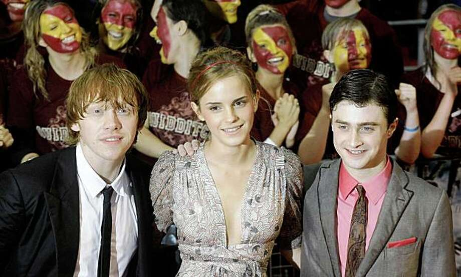 Cast Members, from left, Rupert Grint, Emma Watson and Daniel Radcliffe pose for photographers as they arrive at the world premiere of the film Harry Potter and the Half Blood Prince at a cinema in London, Tuesday, July 7, 2009.  (AP Photo/Matt Dunham) Photo: Matt Dunham, AP