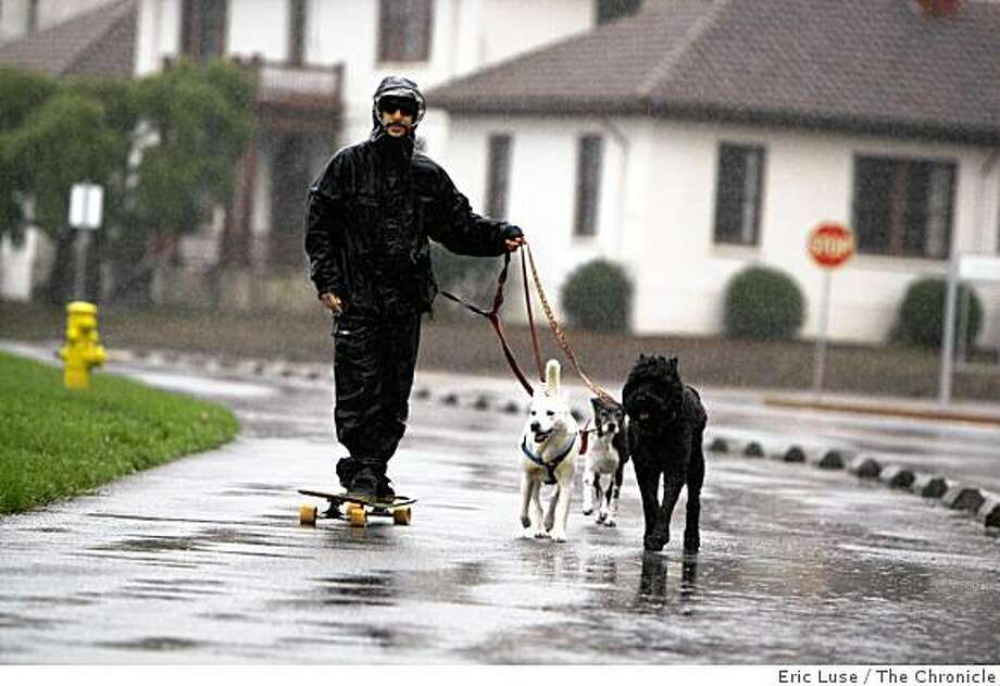 Dog walker Brad Meyer on a skateboard gets a tow from his dogs along Crissy Field during a downpour in San Francisco photograpghed  on Monday, November 3, 2008. Photo: Eric Luse, The Chronicle