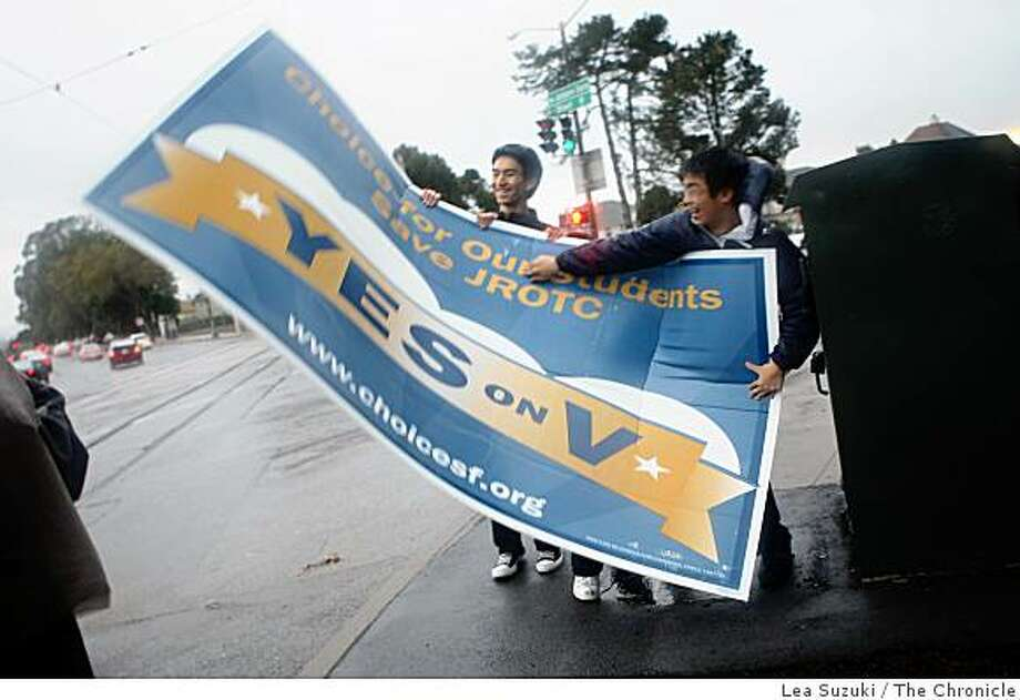 "Lowell High School JROTC students Raymond Zhou, 17 (l to r), Michelle Marcaida, 15 (feet showing in middle under sign) and Stanley Lau, 17 try to get a grip on their ""Yes on V"" sign as it catches a gust of wind while they and some classmates stand at the corner of Sloat and Junipero Serra Boulevards  trying to drum up support on Monday, November 3, 2008 in San Francisco, Calif. Photo: Lea Suzuki, The Chronicle"