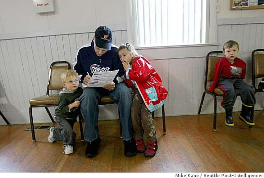 Bob Rossilli, of Sammamish, fills out his ballot with his children Bobby, 3, left, and Emma, 5, at the Happy Valley Grange in northeast King County, Wash., on Tuesday, November 4, 2008. Mr. Rossilli voted for McCain while his children and wife are Obama supporters.