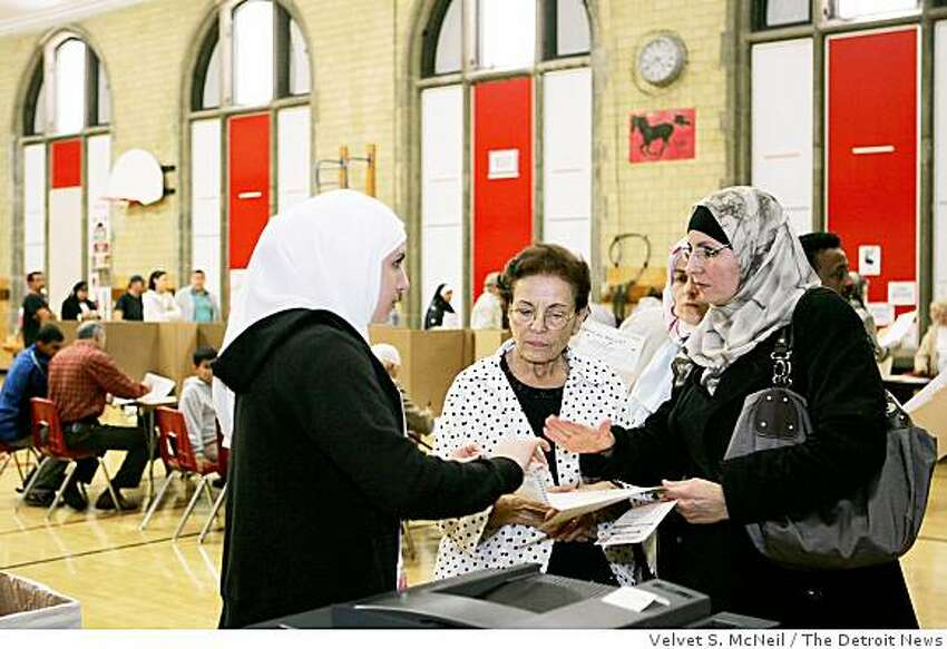 Amal Abou-Arabi, poll worker, left, speaks with Charlene Shannir, right, as she helps her mother Rose Saleh, 79, center, cast her ballot on Election Day in Dearborn, Mich.