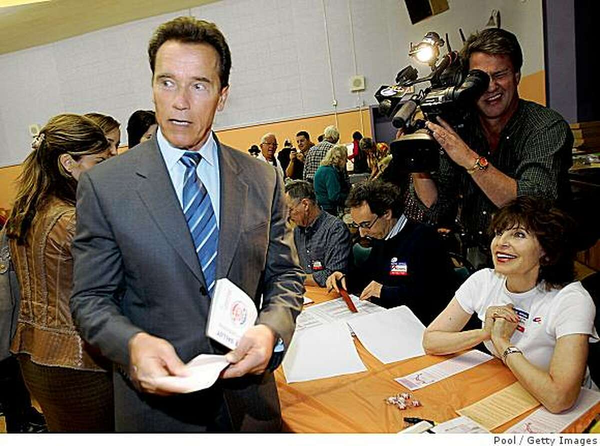 California Gov. Arnold Schwarzenegger C) heads towards the voting booth at Kenter Canyon Elementary school in Brentwood November 4, 2008 in Los Angeles, California.
