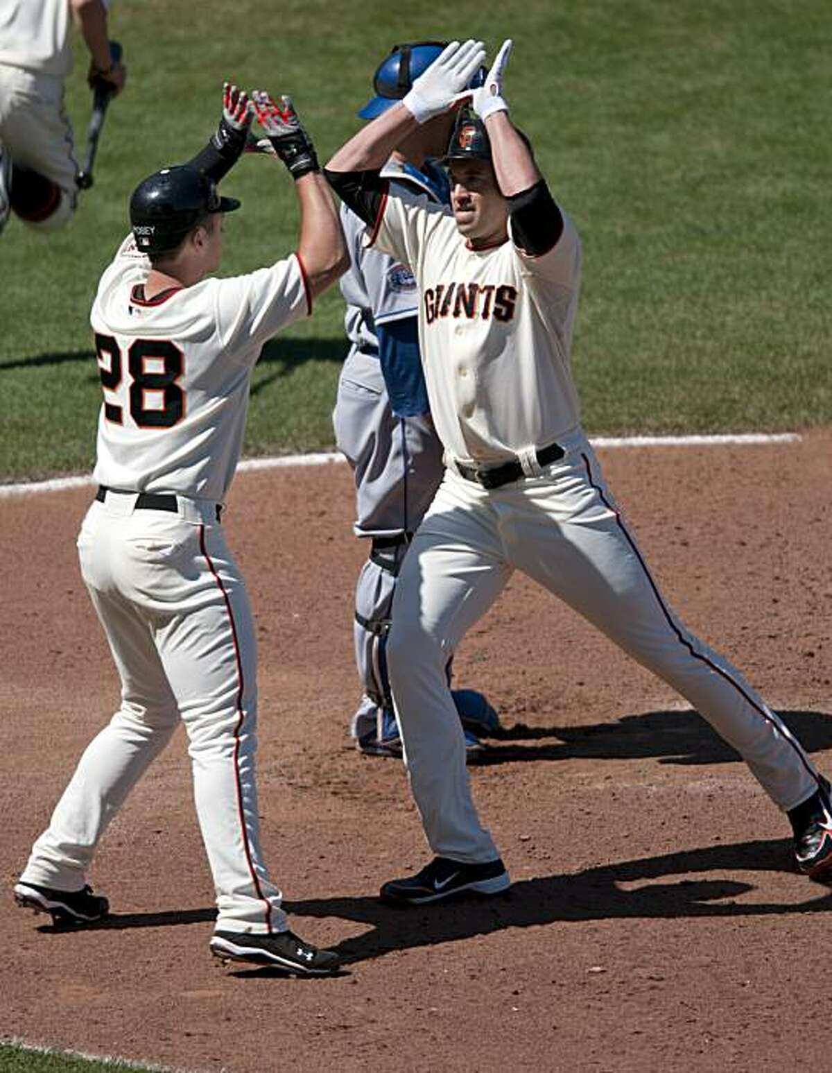 Pat Burrell gets a huge congratulations from Buster Posey as he crosses home plate after blasting a two-run home run in the bottom of the eighth inning Saturday.