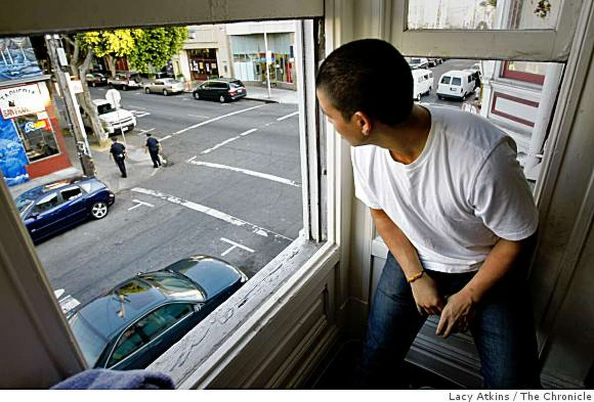 Benjamin Castaneda, 20 years old, looks outside a window from his home where he often sees norteno members hanging out, Wednesday Oct. 22, 2008, in San Francisco, Calif.