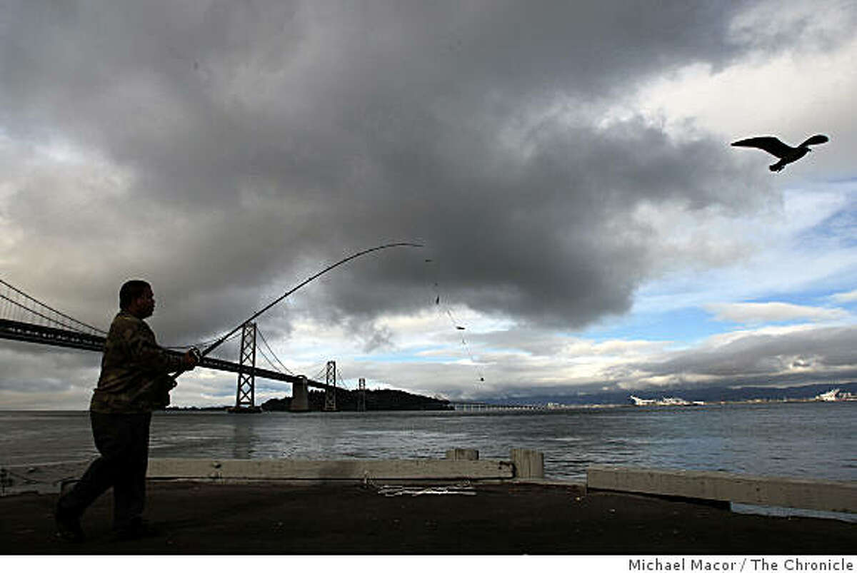 Francisco Bracamonte of Daly City,fishes off of Pier 30 in San FRancisco, Calif., near the Bay Bridge, on Thursday Oct. 2, 2008, as mid-level clouds roll into San Francisco Bay bringing what forecasters are calling a significant rain storm due to arrive on Friday afternoon.