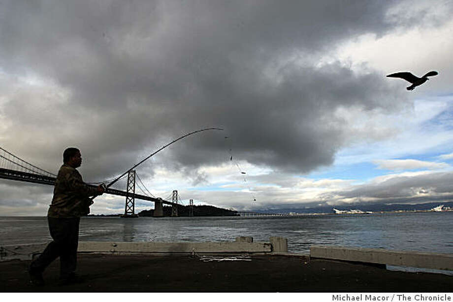 Francisco Bracamonte of Daly City,fishes off of Pier 30 in San FRancisco, Calif.,  near the Bay Bridge, on Thursday Oct. 2, 2008, as mid-level clouds roll into San Francisco Bay bringing what forecasters are calling a significant rain storm due to arrive on Friday afternoon. Photo: Michael Macor, The Chronicle
