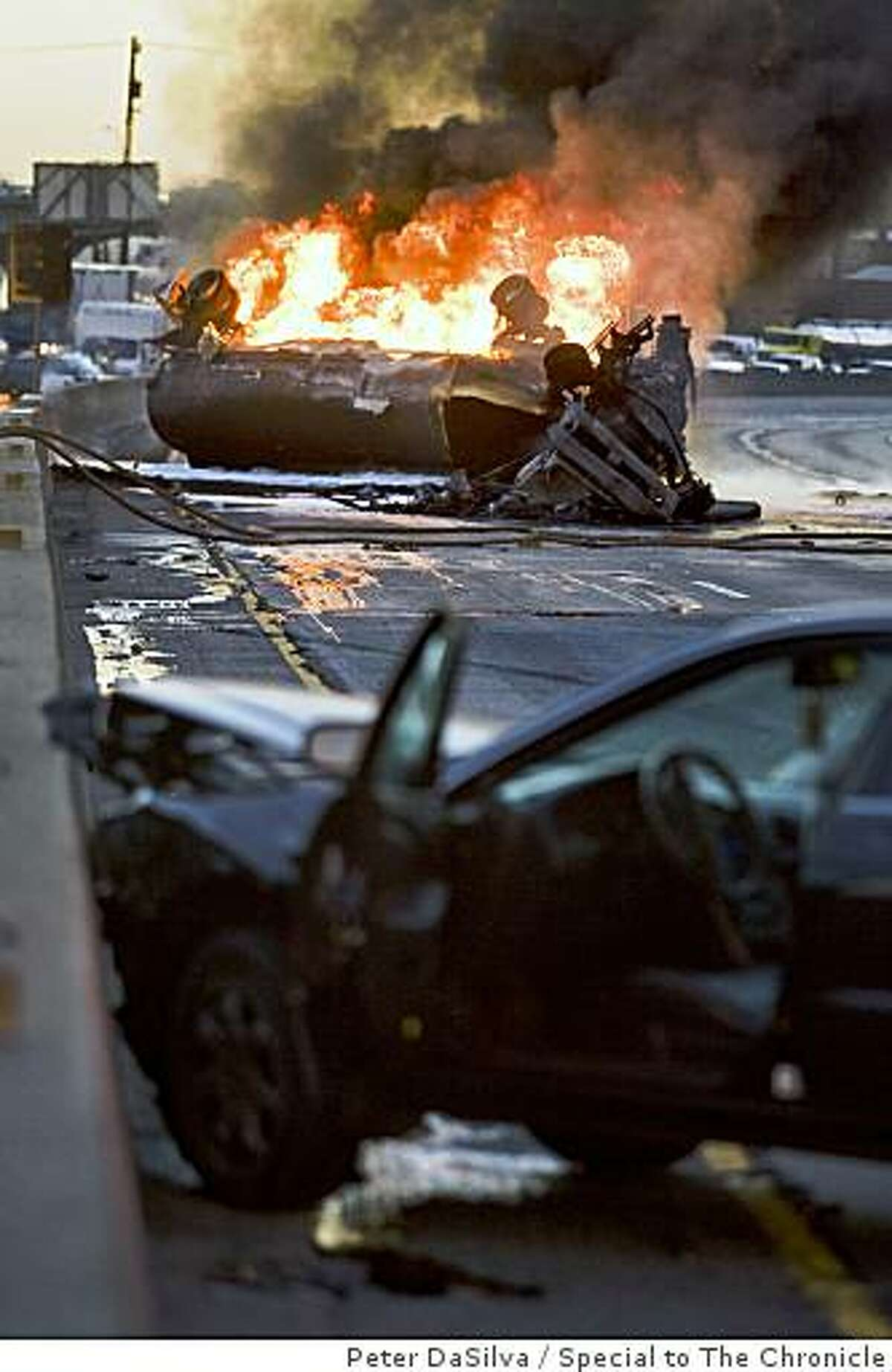 The wreck of a black sedan involved in the over turned tanker truck burning out of control sits along south bound HWY 880 in Oakland California, Oct. 22, 2008.