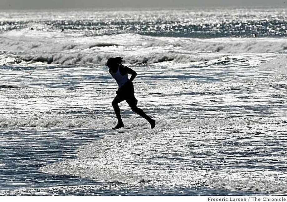 A beach goer runs through the surf at Ocean Beach in San Francisco, Calif., on Wednesday October 22, 2008. Photo: Frederic Larson, The Chronicle