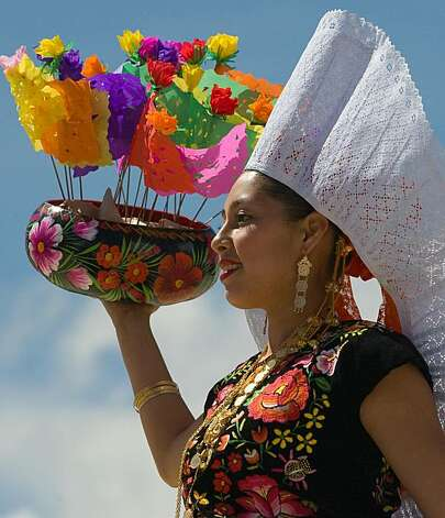 A dancer from Ixtepec city performs during the Guelaguetza celebration on July 27, 2009 in Oaxaca, Mexico. The Guelaguetza is a festival held once a year which gathers music, dances, gastronomy and handicrafts of different ethnic groups and tribes of the state of Oaxaca. AFP PHOTO/Omar Torres (Photo credit should read OMAR TORRES/AFP/Getty Images) Photo: Omar Torres, AFP/Getty Images