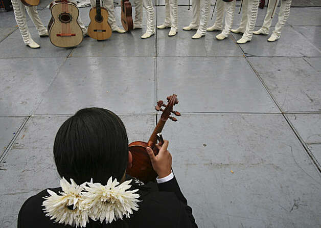 A female Mariachi sits in front of a group of Mariachi musicians during the International Mariachi Festival in Las Cabanas, Guadalajara, Mexico Sunday, Aug. 30, 2009. A total of 549 musicians got together to win the record for playing several songs in just over 10 minutes. A representative of the Guinness Book of World Records, Stuart Claxton, made it official at the Festival. The old record belonged to 520 mariachis who performed in San Antonio, Texas, in 2007, said Francisco Beckman, an organizer of the record-breaking attempt. (AP Photo/Carlos Jasso) Photo: Carlos Jasso, AP