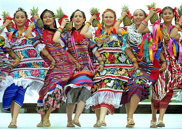 "OAXACA, MEXICO:  Dancers wearing traditional dresses perform the ""Pineapple Flower"" dance in Oaxaca, Mexico, 22 July, 2002. The dance, which originated in the Tuxtepec region of Mexico' state of Oaxaca, is part of the ""Guelaguetza"" Festival, attended by thousands of national and international tourist. The festival exhibits the seven regions that compose the southern Mexican state.   AFP PHOTO/Carlos SALINAS (Photo credit should read CARLOS SALINAS/AFP/Getty Images) Photo: Carlos Salinas"