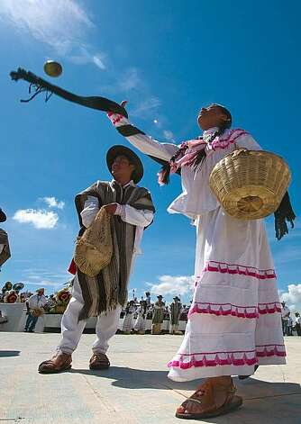 Dancers from San Pedro Ayutla throw fruits to spectators during the Guelaguetza celebration on July 27, 2009 in Oaxaca, Mexico. The Guelaguetza --which in Zapotec languaje means the act of participating in a community celebration-- is a festival held once a year which gathers music, dances, gastronomy and handicrafts of different ethnic groups and tribes of the state of Oaxaca. AFP PHOTO/Omar Torres (Photo credit should read OMAR TORRES/AFP/Getty Images) Photo: Omar Torres, AFP/Getty Images
