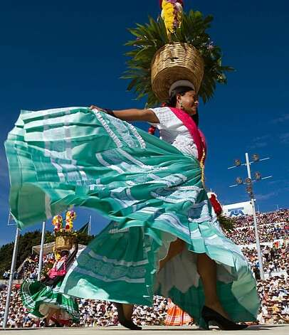 A dancer from San Jeronimo Tecoatl performs during the Guelaguetza celebration on July 27, 2009 in Oaxaca, Mexico. The Guelaguetza is a festival held once a year which gathers music, dances, gastronomy and handicrafts of different ethnic groups and tribes of the state of Oaxaca. AFP PHOTO/Omar Torres (Photo credit should read OMAR TORRES/AFP/Getty Images) Photo: Omar Torres, AFP/Getty Images