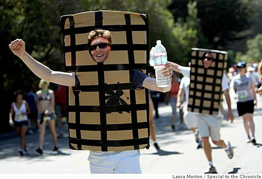 Two runners dressed as fly traps make their way towards the finish line during the Bay to Breakers. Photo: Laura Morton, Special To The Chronicle