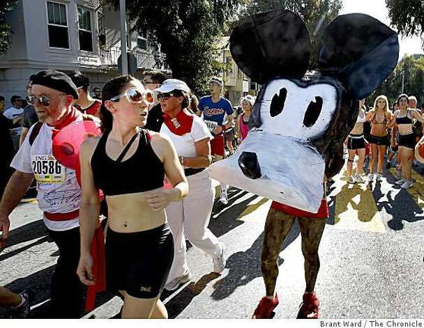 A woman looked back at an odd mouse outfit worn by a runner Sunday. The 98th running of the Bay to Breakers in San Francisco, CA featured a police crackdown on public drinking. Photo: Brant Ward, The Chronicle
