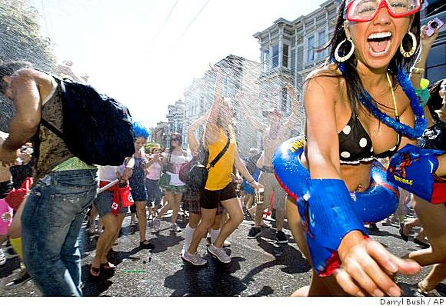 Unidentified runners enjoy water being sprayed on them as they ascend the Hayes Street hill during the 98th running of the Bay to Breakers race in San Francisco, Sunday, May 17, 2009.  The annual race, which attracts as many as 70,000 runners, is well known for its participants wearing wacky costumes. (AP Photo/Darryl Bush) Photo: Darryl Bush, AP