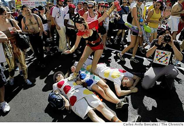 "Anna Lin of San Francisco, steps on ""Twister"" runners (left to right) Ryan Avery, Erin Esko, and Kermit Goodman, during the 98th running of the Bay to Breakers. Photo: Carlos Avila Gonzalez, The Chronicle"