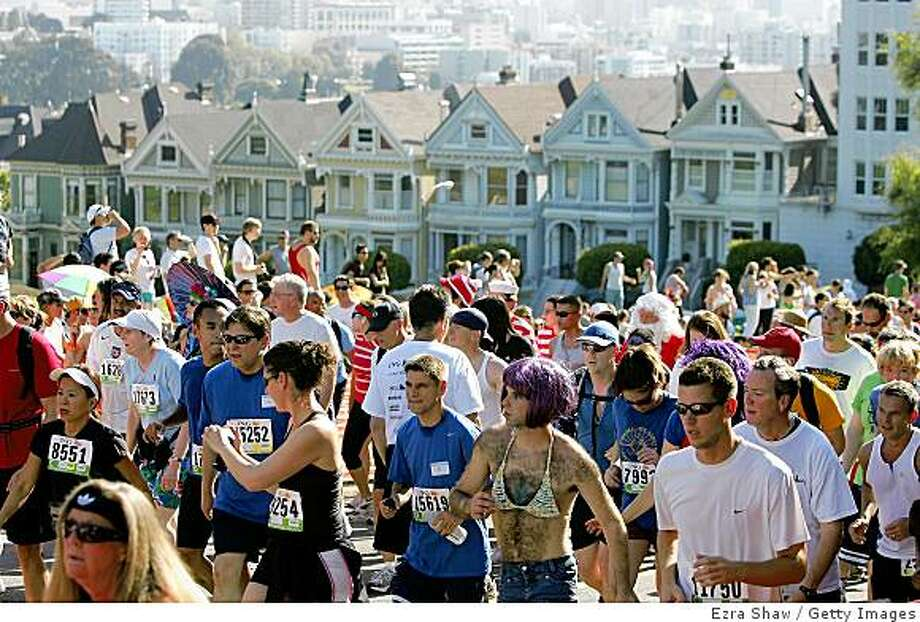 "SAN FRANCISCO - MAY 17:  Participants run up Hayes Street Hill with the backdrop of the city's ""Painted Ladies"" houses during the ING Bay to Breakers race May 17, 2009 in San Francisco, California.  Now in its 98th year, the ING Bay to Breakers 12K is one of the world's largest and oldest footraces, featuring world-class athletes in addition to costumed runners.  (Photo by Ezra Shaw/Getty Images) Photo: Ezra Shaw, Getty Images"