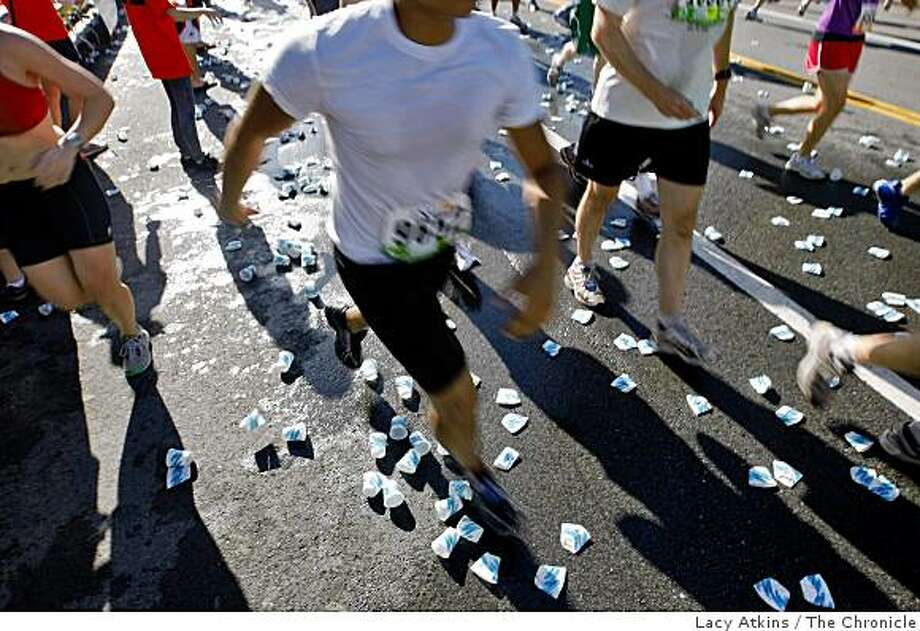 Thousands of people run through the water stands leaving trash along the Oak Street during the Bay to Breakers. Photo: Lacy Atkins, The Chronicle