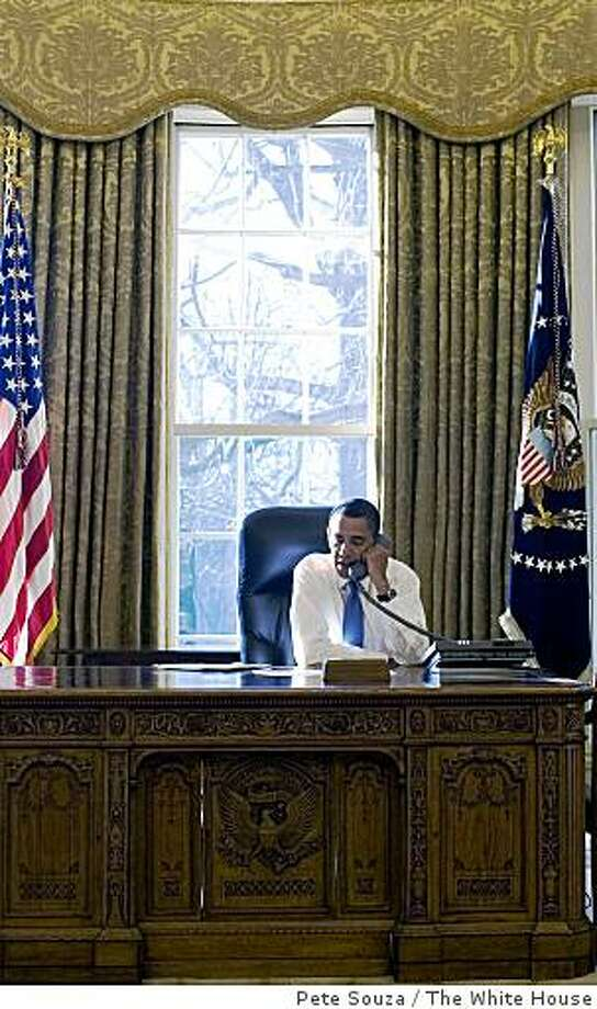 (NYT46) WASHINGTON -- Jan. 21, 2009 -- OBAMA-13 -- President Barack Obama  at his desk in the Oval office of the White House, in Washington, Wednesday, Jan. 21, 2009.  The photo was released by the White House. Wednesday was Obama's first full day as president. (Pete Souza/The White House via The New York Times) EDITORIAL USE ONLY Photo: Pete Souza, The White House