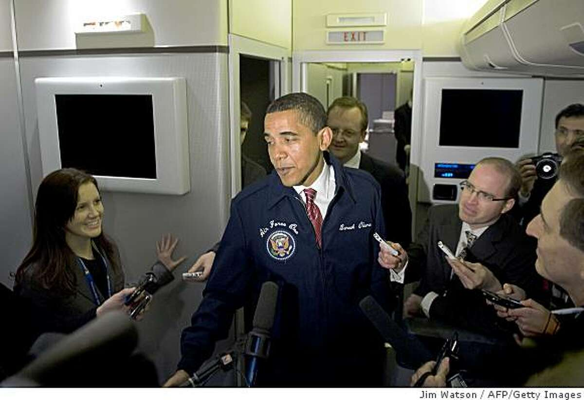 US President Barack Obama (C) comes back to the press cabin to show off his new coat shortly after boarding Air Force One for his first flight on the presidential aircraft February 5, 2009 at Andrews Air Force Base, MD. Obama is en route to the House Democrats Conference in Williamsburg, Virginia. AFP PHOTO / Jim WATSON (Photo credit should read JIM WATSON/AFP/Getty Images)