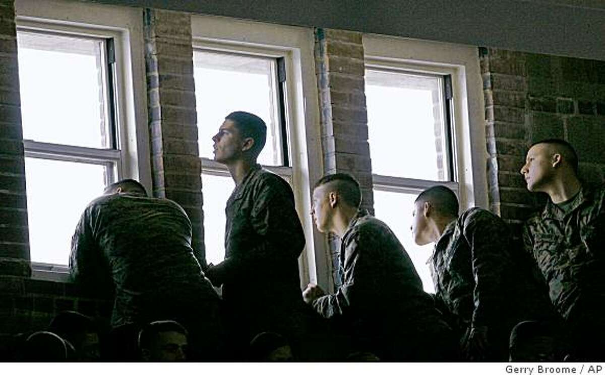 Marines peer though a window awaiting the arrival of President Barack Obama at Camp Lejeune, N.C., Friday, Feb. 27, 2009. (AP Photo/Gerry Broome)