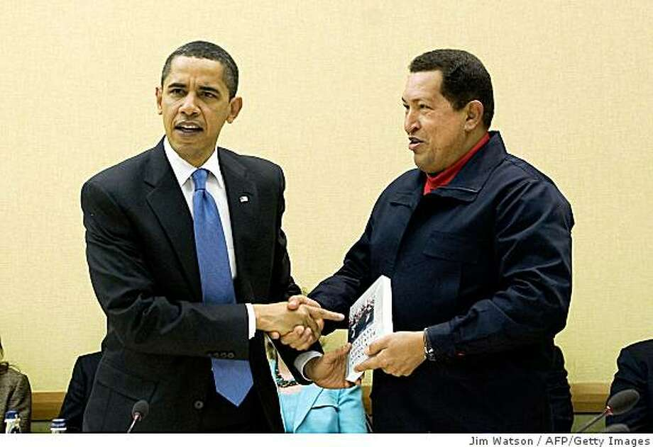 TOPSHOTS Venezuelan President Hugo Chavez (R) gives a book, 'The Open Veins of Latin America' of Uruguayan writer Eduardo Galeano to US President Barack Obama (L) during a multilateral meeting to begin during the Summit of the Americas at the Hyatt Regency in Port of Spain, Trinidad April 18, 2009.                   AFP  PHOTO/Jim WATSON (Photo credit should read JIM WATSON/AFP/Getty Images) Photo: Jim Watson, AFP/Getty Images