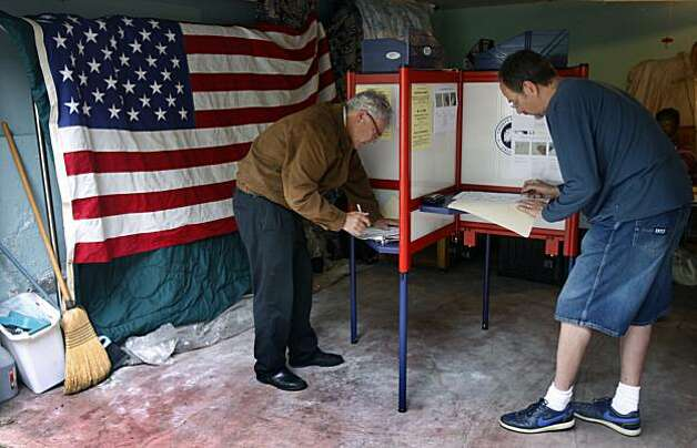Mark Jansen (left) and Thomas Dawson vote at a polling place in a garage on Eunice Street in Berkeley on Tuesday. Photo: Paul Chinn, The Chronicle