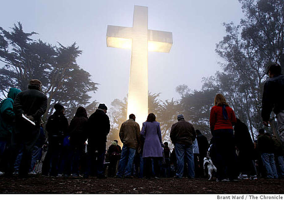 People gathered in the early morning light before the 100 foot cross. Nearly 200 people turned out atop San Francisco's Mount Davidson for the traditional sunrise Easter service Sunday April 12, 2009. Photo: Brant Ward, The Chronicle