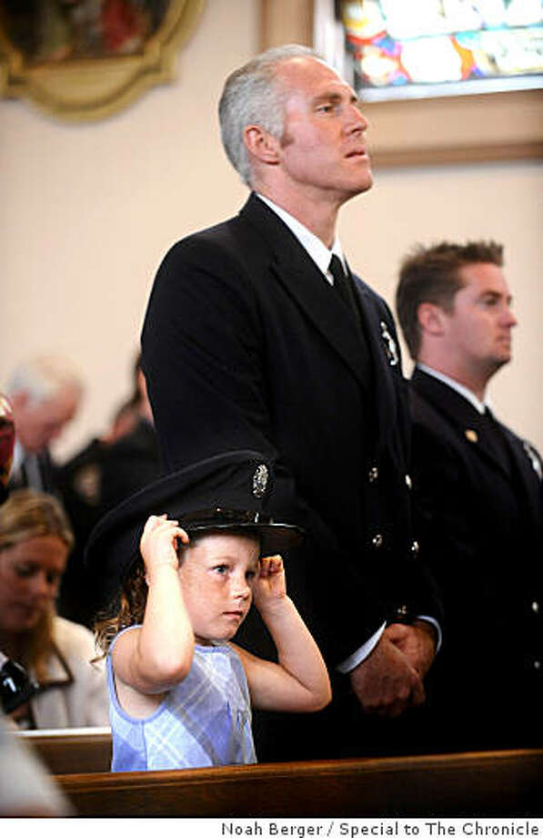 Veronica Maguire, 4, dons her dad?s cap while attending the 61st Annual Police/Fire Memorial Mass on Sunday, Sept. 7, 2008, in San Francisco. Her father, firefighter Steve Maguire, stands beside her. Photo: Noah Berger, Special To The Chronicle