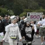 Mary Pellow of San Francisco and Bambi Moise of San Jose move along John F. Kennedy Drive dressed as the S&P 500 during Bay to Breakers in San Francisco on Sunday.