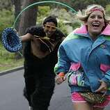 Brian Goldberg of Davis playfully chases Diana Paasch of San Luis Obispo in Golden Gate Park during Bay to Breakers in San Francisco on Sunday.
