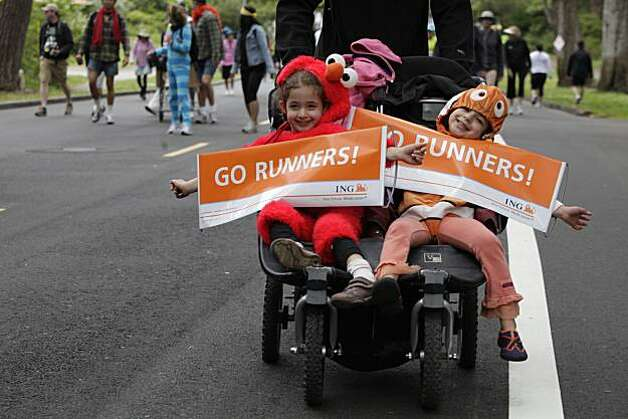 "Kallen and Lainey Wank, both 5, hold signs saying, ""Go Runners!"" as their father, Jon Wank, pushes them through Golden Gate Park during Bay to Breakers in San Francisco on Sunday. Photo: Lea Suzuki, The Chronicle"