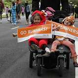 "Kallen and Lainey Wank, both 5, hold signs saying, ""Go Runners!"" as their father, Jon Wank, pushes them through Golden Gate Park during Bay to Breakers in San Francisco on Sunday."