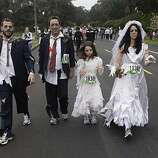 Michael Rochetti of San Francisco, David Green of Los Angeles, Sofia Rochetti, 8, of San Francisco and Roberta Rochetti of San Francisco make their way through Golden Gate Park during Bay to Breakers in San Francisco on Sunday.
