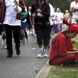 Olivia Bronson of San Rafael checks her phone as she tries to meet up with others in Golden Gate Park during Bay to Breakers in San Francisco on Sunday.