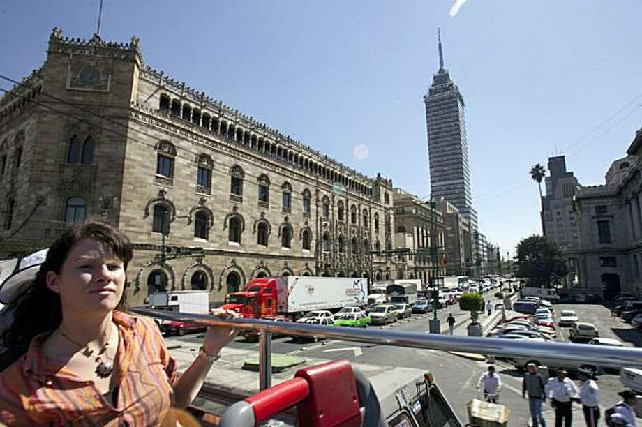 A tourist rides a double decker Turibus passing the Latin America Tower in downtown Mexico City. Photo: Gregory Bull, AP