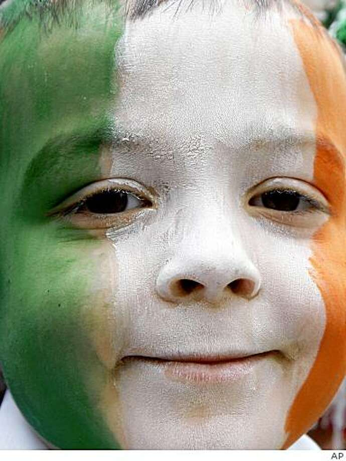 A boy watches the St Patrick's day parade in Dublin, Ireland, Tuesday, March, 17, 2009. An estimated 500,000 Irish people, immigrants and tourists lined up along a parade route in Dublin on Tuesday to celebrate St. Patrick's Day _ a national holiday dimmed this year by an economic recession and rising violence. Ireland faces its sternest economic challenges in decades. Unemployment has soared above 10 percent, the government is imposing severe tax increases and cuts to combat a budget deficit, and the national mood is struggling amid rising emigration and violence. Photo: AP