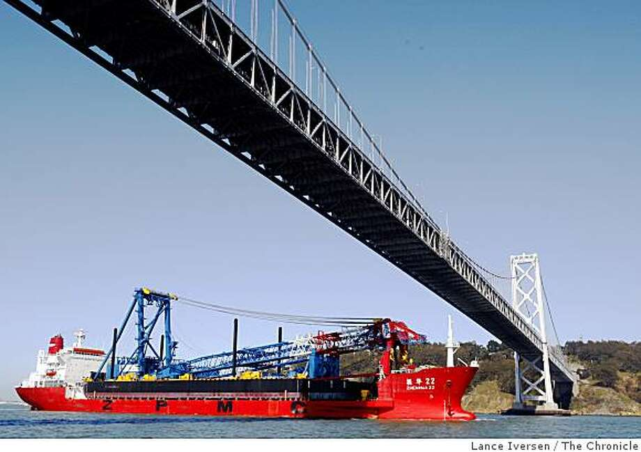 A massive shear leg crane mounted on a barge passed under the San Francisco-Oakland Bay Bridge Thursday, March 12, 2009. The barge measures 400 by 100 feet and was custom built in Portland Ore. The barge was outfitted with the massive six story high carne dubbed the Left Coast Lifter in Shanghai China, then ferried across the Pacific aboad the 750-foot-long partially submersible ship Zhen Hua 22. The crane will later be used to erect the signature 525-foot bridge tower. Photo: Lance Iversen, The Chronicle