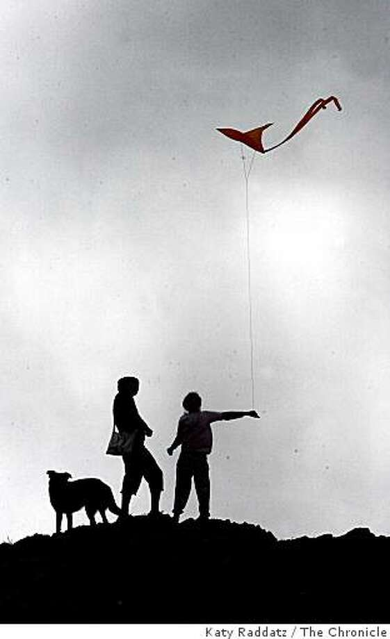 "In the windy foggy afternoon light atop Bernal Hill Park, 9 year old Chloe Visser-Keough, right, her mother Angela Visser-Keough, center, and their dog, ""Eli""  left, all of San Francisco,  get their orange kite airborne,  in San Francisco, Calif. Sunday,  Aug. 3, 2008. Photo: Katy Raddatz, The Chronicle"