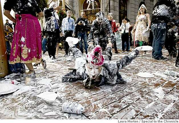 Lee Harvey Roswell pulls Anne-Marie Goco through the sidewalk covered in shaving cream during a flash mob pie fight at the Powell and Market cable car turn around in San Francisco, Calif., on Thursday, March 5, 2008. Photo: Laura Morton, Special To The Chronicle